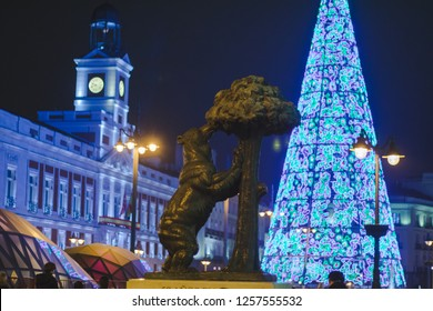 Madrid, Spain -5 december, 2018: The bear with the madroño tree, symbol of the city of Madrid during Christmas holidays with Christmas tree light and Door of the Sun (Puerta del Sol) in the background