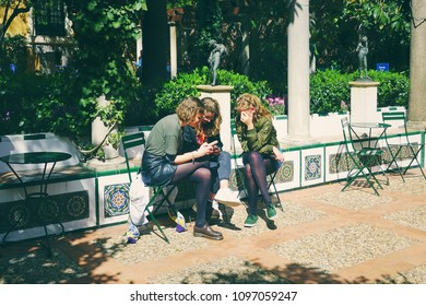 MADRID, SPAIN - APRIL 04, 2018: three girls are sitting and chatting in the traditional Spanish courtyard at the territory of the Museum Sorolla.