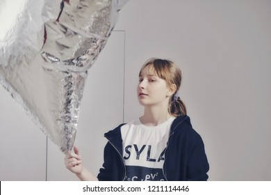 "MADRID, SPAIN - APRIL 05, 2018: A girl playing with ""silver clouds"" in the CaixaForum Madrid at the exibition Andy Warhol ""Warhol. Mechanical Art."""