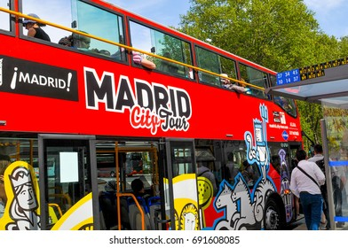 Madrid, Spain - April 10, 2016: Tourists embark red tour bus in front of Prado Museum in Madrid, Spain