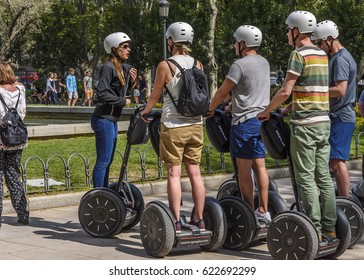 MADRID, SPAIN - APRIL 12, 2017: A group of tourists, uploaded on segways, listens to the woman who is the  guide.