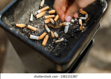 Madrid, Spain - April 15, 2019:  Big ashtray with cigarette butts. A smoker shakes off the ash in an ashtray. Extinguished old cigarette butts from cigarettes, iridescent smell, harm of smoking, hand