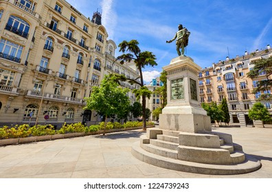 Madrid, Spain. Area of Plaza de Las Cortes with monument in honor of famous Spanish writer Miguel de Cervantes and cosy square green trees bushes among houses. Urban summer landscape with landmark.