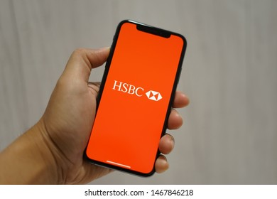 Madrid, Spain - August 01, 2019; HSBC Iphone XS Application on a Boys Hand with Wooden Background