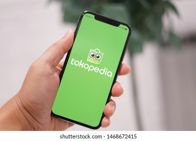 Madrid, Spain - August 02, 2019; Tokopedia Iphone XS Application with a Green Leaves Background
