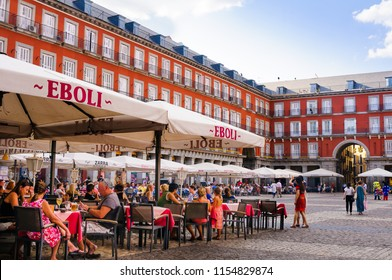 MADRID, SPAIN - AUGUST 10, 2018: People sitting at a terrace in the Plaza Mayor of Madrid