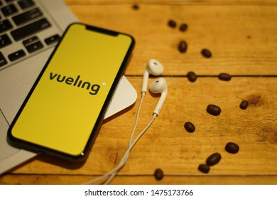 Madrid, Spain - August 10, 2019; Vueling Iphone XS Application on Macbook with Earpiece on a Rustic Wooden Table with Coffebean