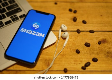 Madrid, Spain - August 13, 2019; Shazam Iphone XS Application on Macbook with Earpiece on a Rustic Wooden Table with Coffebean