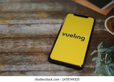 Madrid, Spain - August 14, 2019; Vueling Iphone XS Application with a Cup of Coffee on a Rustic Wooden Table