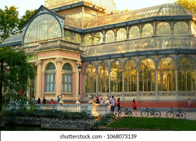 """MADRID, SPAIN - AUGUST 15, 2014: Unknown people walking near ThePalacio de Cristal.""""Crystal Palace"""" is a glass and metal structure located inMadrid'sBuen Retiro Park. The architect wasRicardo Vel"""