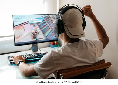 Madrid, Spain - August 15, 2018: Teenager playing Fortnite video game on PC. He is raising his fist in a victory gesture. Fortnite is an online multiplayer video game developed by Epic Games