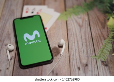 Madrid, Spain - August 19, 2019; Mi Movistar Green Iphone XS Application with Earpiece and Aces Card on a Pallet Wood Table