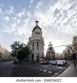 MADRID, SPAIN - AUGUST 2017: Cars waiting for traffic-light at the street cross Calle de Alcala and Gran Via at sunny evening in Madrid, Spain. Gran Via unofficially considered main street of Madrid