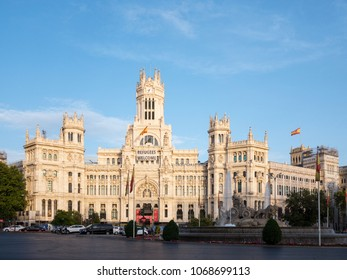 """MADRID, SPAIN - AUGUST 2017: Fountain """"Fuente de La Diosa Cibeles"""" and Cibeles Palace (formerly the Palace of Communication) with """"Refugees Welcome"""" flag on the facade at the Plaza de Cibeles"""