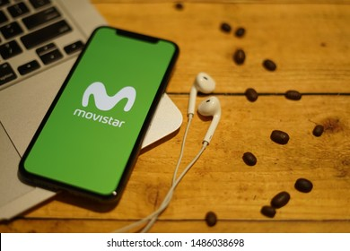 Madrid, Spain - August 23, 2019; My Moviestar Green Iphone XS Application on Macbook with Earpiece on a Rustic Wooden Table with Coffebean