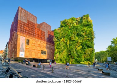 MADRID, SPAIN - AUGUST 31, 2018: Vertical garden and CaixaForum Madrid, which is a museum and cultural center, constructed in 2007 on base of an abandoned electrical station.