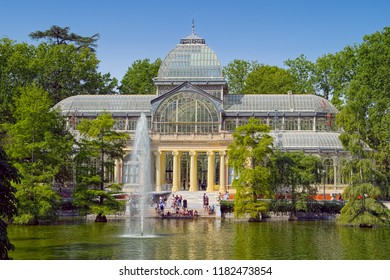 MADRID, SPAIN - AUGUST 31, 2018: Landscape in Retiro Park with view of Palacio de Cristal (Crystal Palace), built in 1887 and now used for art exhibits.
