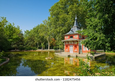 MADRID, SPAIN - AUGUST 31, 2018: Casita Del Pescador (Fisherman's Cottage) stands on small island in middle of pond and was built by King Ferdinand VII in private garden, now is part of Retiro Park.