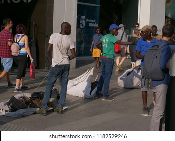 MADRID, SPAIN - AUGUST 31, 2018: Scene with some persons who are seems trying to make illegal sales of goods at pedestrian area of Gran Via street of city center. No digital altering.