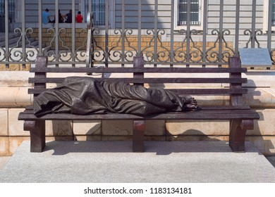 MADRID, SPAIN - AUGUST 31, 2018: Homeless Jesus - a bronze sculpture by Canadian sculptor Timothy Schmalz, installed in 2016 near the entrance to Almudena Cathedral of Madrid, Spain.