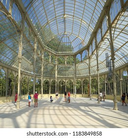 MADRID, SPAIN - AUGUST 31, 2018: Visitors inside of Palacio de Cristal (Crystal Palace), it's built in 1887 in Retiro Park as art venue and exibitions.