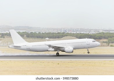 MADRID, SPAIN - AUGUST 8th 2015: Fully white plane Airbus A320, of SmartLynx airline, is landing on Madrid - Barajas, Adolfo Suarez airport, on August 8th 2015. Cloudy day of summer