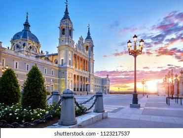 Madrid, Spain. Cathedral Santa Maria la Real de la Almudena at Plaza de la Armeria. Famous landmark with sunset sun, flowers and green bush. Street lamps with illumination and picturesque sky.