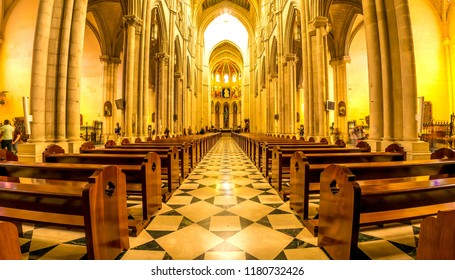 MADRID, SPAIN - CIRCA MARCH 2017: View on the architecture of a catholic church interior as people pass by between pews circa March 2017 in Madrid, Spain.