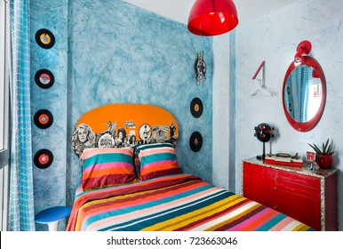 Madrid, Spain. Circa September 2017. Vintage bedroom with a 60s clock, desk, records,mirror, colorful bedcover and retro lamp