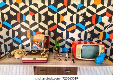 Madrid, Spain. Circa September 2017.Vintage decoration with geometric wallpaper, retro tv, old portable record player, telephone and ceramics.