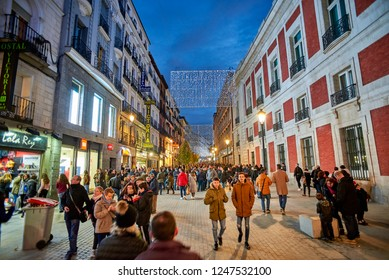 Madrid, Spain - December 1, 2018. People walking on the Calle de Carretas street at nightfall illuminated by christmas lights. View from Puerta del Sol square.