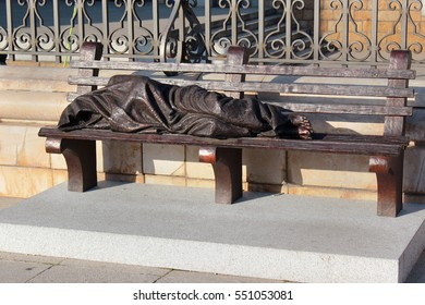 MADRID, SPAIN - DECEMBER 13, 2016: Sculpture of Homeless Jesus designed by Timothy Schmalz. Set in front of the Catholic Cathedral Santa Maria la Real de La Almudena in Madrid.