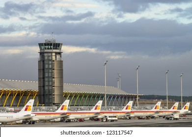 MADRID, SPAIN - DECEMBER 16: View of one of the airport control towers of Madrid Barajas, and a group of Iberia planes parked in Madrid on December 16, 2012. Iberia is the largest spanish airline.