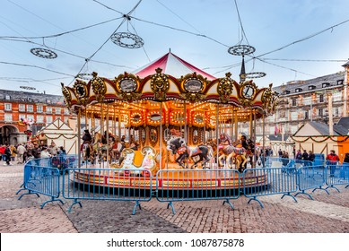 MADRID, SPAIN - DECEMBER 20, 2010: People have fun in Christmas time on the carrousell for children in the evening at the plaza de Mayor in Madrid , Spain.