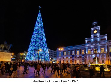 Madrid, Spain, December 2018. Crowded Puerta del Sol square at nightfall illuminated by christmas lights and a shinny christmas tree.