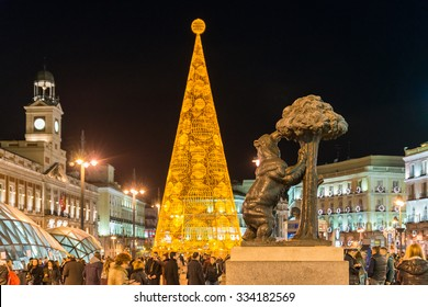 MADRID, SPAIN - DECEMBER 9, 2014: Madrid Symbol: The Bear and The Strawberry Tree with Out of Focus Golden Christmas Tree background at La Puerta del Sol Square Full of Tourists at Night in Winter