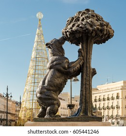 MADRID, SPAIN - DECEMBER 9, 2014: Madrid Symbol, The Bear and Strawberry Tree with Out of Focus Golden Christmas Tree at La Puerta del Sol Square Full of Tourists under clear blue sky new year eve