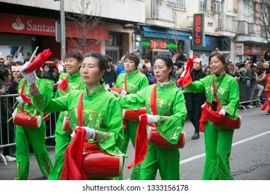 Madrid, Spain - February 10, 2019: Women dressed in green with instruments and dancing in celebration of Chinese New Year