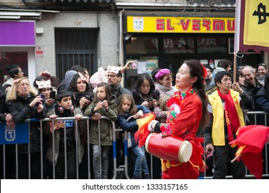 Madrid, Spain - February 10, 2019: Women dressed in red dancing and playing instruments in celebration of Chinese new year parade