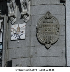 Madrid, Spain - February 12, 2019: A shot in Puerta del Sol of the Plaque Asegurada de Incendios 1861, next to the hand painted street sign of Sol.