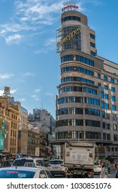 Madrid, Spain - February 20, 2018: Morning heavy traffic and Iconic edificio Carrion building. Located in Gran Via and Jacometrezo street junction, in front of Plaza de Callao Square.