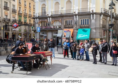 Madrid, Spain - February 21, 2014: three street musicians perform for the public in the 'Puerta del Sol' in Madrid for a few coins.