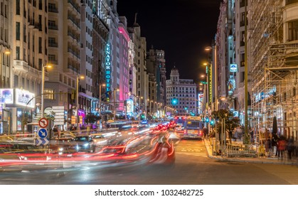 Madrid, Spain - February 23, 2018: Motion blurred people and Car trails. Night heavy traffic in Gran Via and Calle Princesa street Junction at Plaza de Espana. Plaza de Callao Square in the back