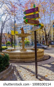 MADRID, SPAIN - JANUARY 1, 2018: View of directing sign and a fountain in Paseo del Prado boulevard, with locals and visitors, in Madrid, Spain