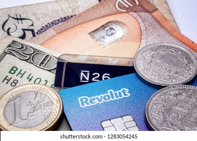 Madrid, Spain / January 13 2019 : Closeup view of banking startups Revolut and N26 generic cards, some ntes and coins.