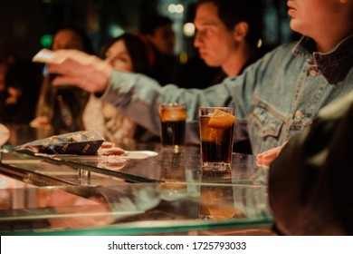 """Madrid, Spain - January 26, 2020:People having drinks inside Mercado de San Miguel (""""Market of San Miguel""""), a covered market in Madrid with stands serving variety of Spanish cuisine, selective focus."""