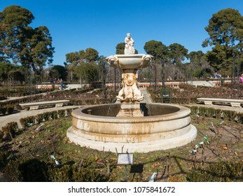 Madrid, Spain - January 27, 2018: Tourists stroll near the fountain of the Garden of Roses in Buen Retiro Park. Parque De Las Rosas in Spanish) in Botanical Garden in Park of Retiro. Madrid, Spain.