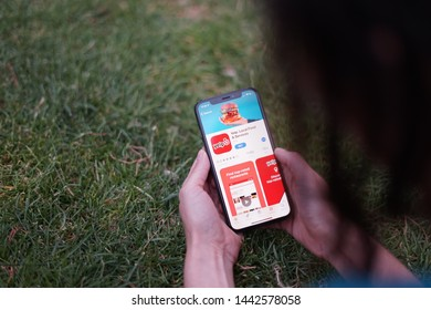 Madrid, Spain - July 05, 2019; Girl Looking at Iphone XS with Yelp Local Food and Services App on the Park