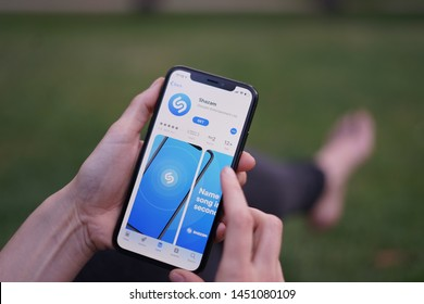 Madrid, Spain - July 15, 2019; Girl Playing Iphone XS with Shazam App on the Grass
