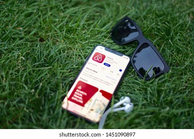 Madrid, Spain - July 15, 2019; Airbnb App on Iphone XS on the Grass with Glasses